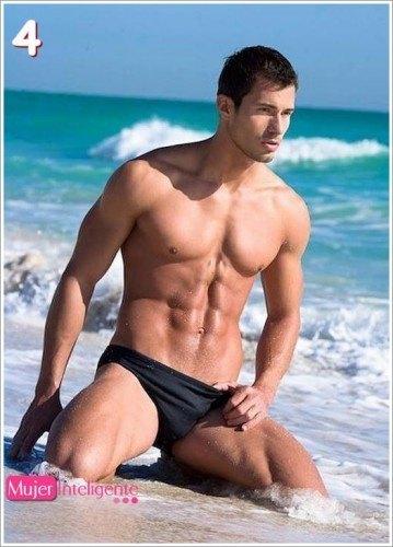 hombre guapo y sexy en la playa marcando bonitos abdominales